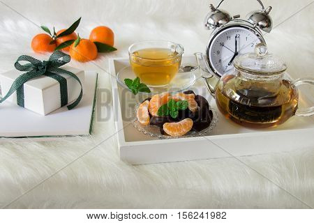 Breakfast from green mint tea in a teapot and a dessert of mandarin slices chocolates on a tray near gift box on white artificial fur background. Happy morning with green mint tea dessert and gift.