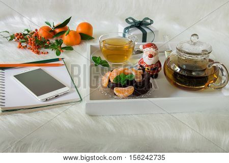 Green mint tea chocolate mandarin slices and Santa Claus on tray near mobile notebook pencil mandarins mountain ash on white artificial fur background. Time break Christmas surprise preparation.