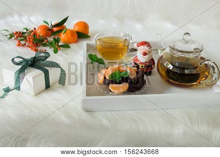 Green mint tea mandarin slices chocolate and Santa Claus statuette on tray near gift box mandarins mountain ash on white artificial fur background. Happy winter day with mint tea dessert gift.