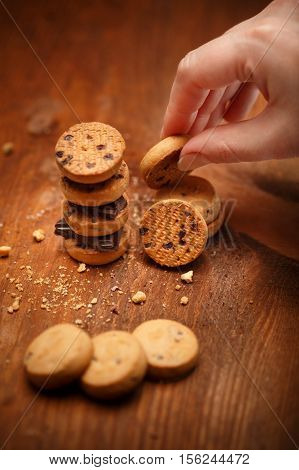 Elegant female hand puts small bisqiut cookies on each other with chocolate pieces between and makes turret at wooden background with chips scattered around. Shallow dof. Focus on hand with cookies.