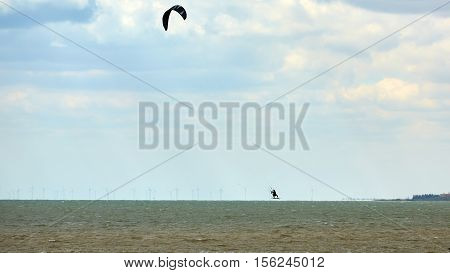 Athletic man jumping on kite surf board on a sea waves.