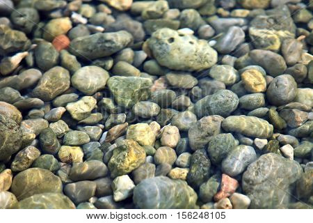 Stone floor under clear water. Pebble bed .. Transparent sea water. Solar patches of light on water. Pebble bottom closeup