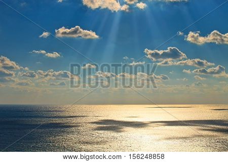 Horizontal seascape. The sun's rays make their way through the gray clouds. Calm sea. No waves. Cloudy blue sky. Landscape without people. Sunny day, bright sun. Seaside the shadow falls from the clouds that float across the sky