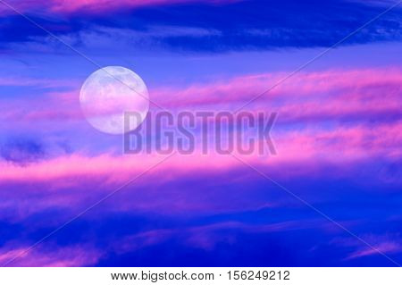 Moon clouds is a vibrant colorful surreal cloudscape with the full moon rising in the sky.