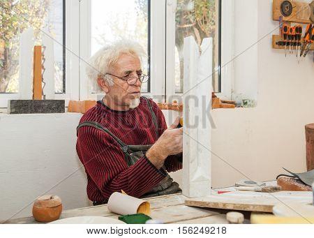 Sculptor In His Studio Handles A Piece Of Marble