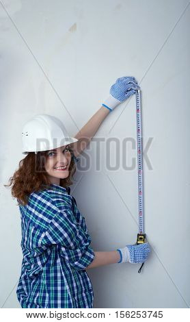 Smiling young woman in casual clothes in front of white unpainted wall in white helmet working with measuring tape, happy people and construction concept