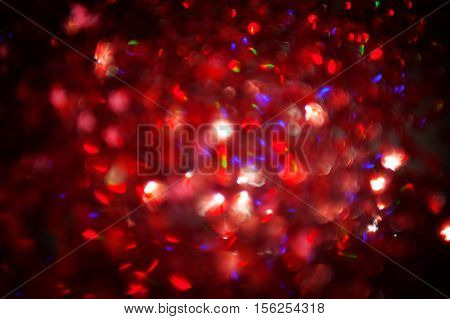 Dark red Festive blur background. Abstract night twinkled bright background with bokeh defocused golden lights. Christmas blurry boke lights