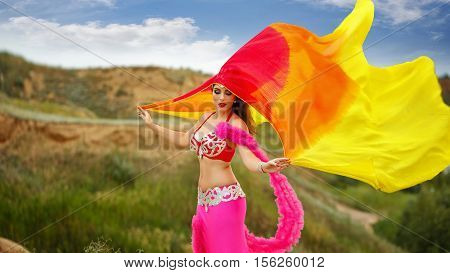 Oriental Beauty belly dancing. Nice girl in national dress dancing with shawl outdoors. Nomads.