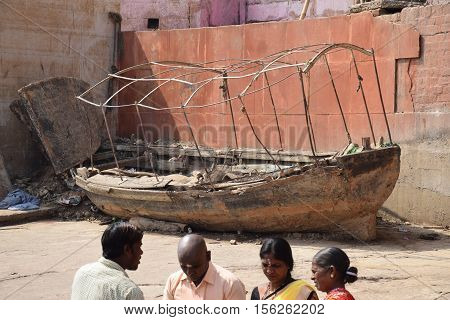 VARANASI, UTTAR PRADESH INDIA - FEBRUARY 17, 2016 - Unidentified indian people and an abandoned wooden boat on the ghats of Varanasi