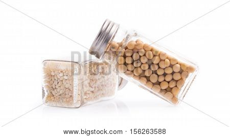 Glass Bottle Of Soybeans And Barley Rice Isolated On White Background