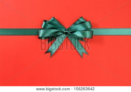 Green Gift Ribbon Bow Straight Horizontal On Red Paper Background