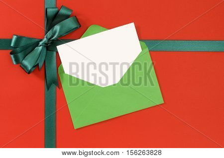 Christmas Or Birthday Card On Red Gift Paper Background With Green Ribbon Bow.