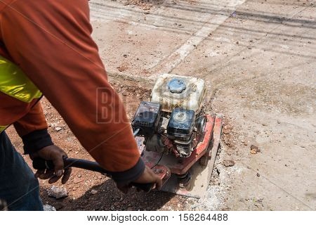 Worker with reversible plate compactor on a roadwork site. Repair cracked Sidewalk