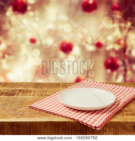 Empty plate on wooden rustic table with tablecloth. Christmas background