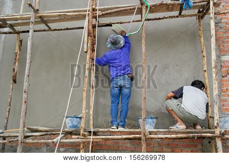 Workman plasters at construction site,Plaster concrete worker at wall of house construction,Building construction site