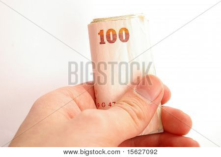 Hand holding a roll of money