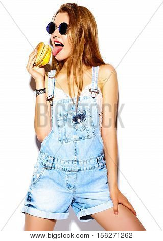 Funny crazy glamor stylish sexy smiling beautiful young blond woman model in summer bright hipster jeans cloth eating hamburger