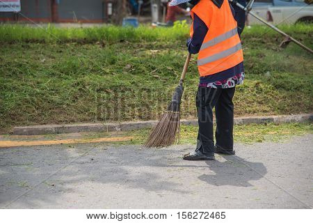 Road sweeper worker cleaning city street with broom tool in Thailand