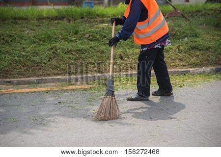 Road sweeper worker cleaning city street with broom tool in Thailand poster