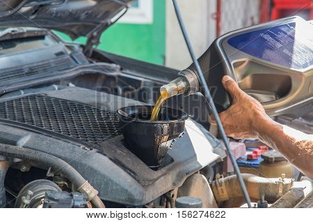 Car maintenance servicing mechanic pouring new oil lubricant into the car engine, A mechanic pours fresh oil into a car engine as part of its maintenance poster