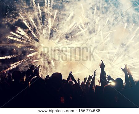 New Year concept - fireworks and cheering crowd celebrating the New year