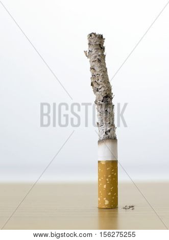 cigarette with long ash on wood table backgroud