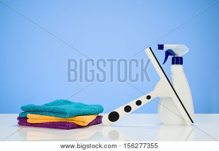 Cleaning product concept blue gradient background with accessories. Assorted products isolated on white and blue backdrop. Studio product shot for advertising, website or blog.