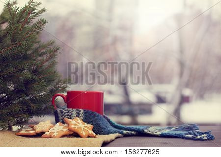 cookies in the form of snowflakes on a table near a Christmas tree and red mug on a background of a winter landscape outside the window / awaiting a holiday poster