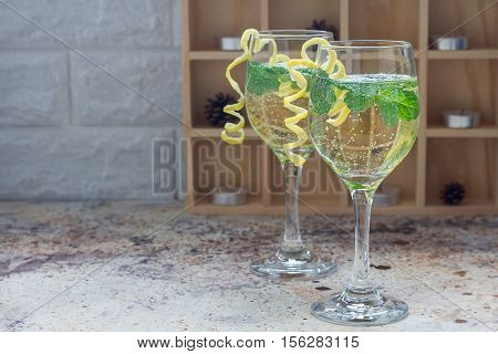 Spritzer cocktail with white wine mint and ice decorated with spiral lemon zest horizontal copy space