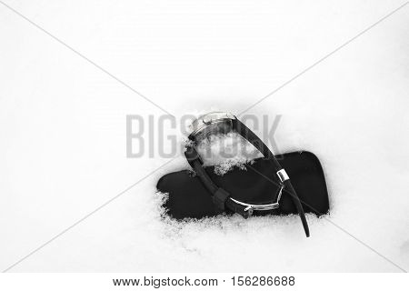 Wrist watch and mobile phone seems broken laid on the snow closeup outdoor shot with particular focus