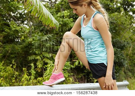 Side Portrait Of Beautiful Blonde Woman Runner With Long Braid In Sportswear Relaxing After Marathon