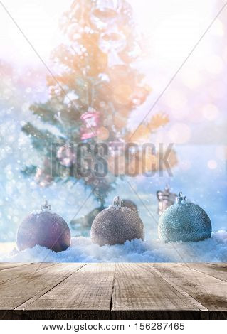 Table Top with fantasy chrismas ball on snow with chrismas tree abstract background. Empty ready for your product display or montage.