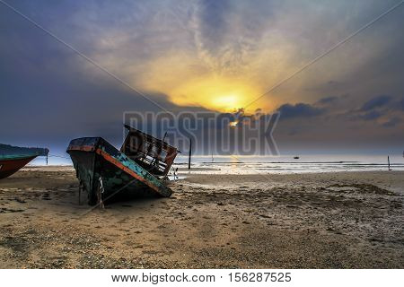 Beautiful sunrise over an old wooden boat sank in the sand