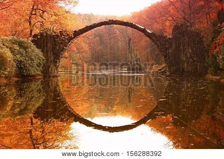 Rakotz bridge (Rakotzbrucke, Devil's Bridge) in Kromlau, Saxony, Germany. Colorful autumn, reflection of the bridge in the water create a full circle