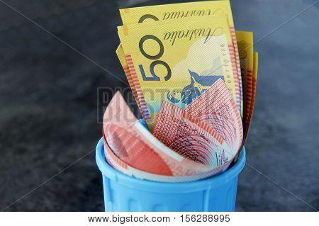 Australian dollars in a blue garbage bin.