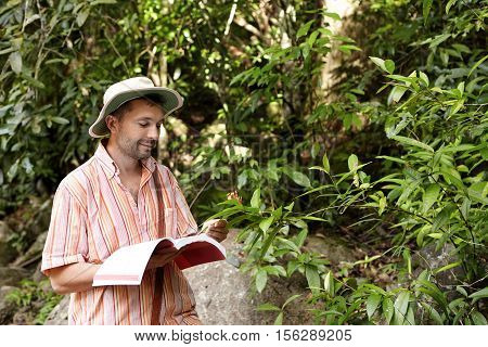 Caucasian Botanist Or Biologist With Stuble Wearing Striped Shirt And Hat Holding Notebook In One Ha