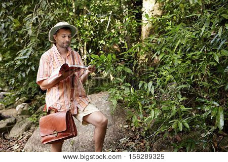 Middle Aged European Biologist Or Ecologist Wearing Hat And Briefcase Reading Notes In His Notebook