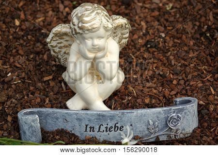 a little angel sculpture decorate in small garden with flowers in front it and a sign - in love - in German