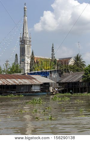 Poor Residential Houses Among Mangrove Forest And A Church In Background