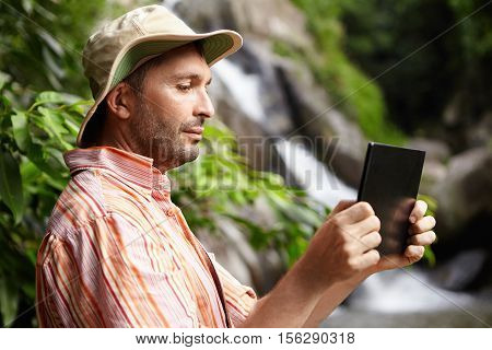 Male Biologist In Striped Shirt And Hat Working In Nature Park, Taking Picture Or Recording Video Of