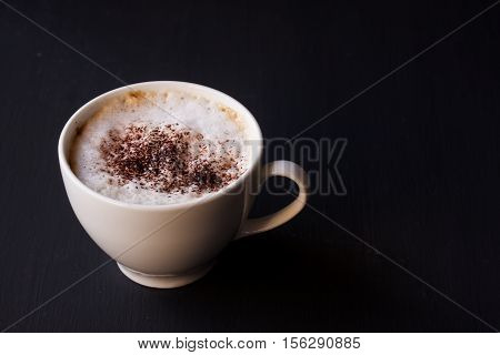 A cup of latte coffee on a black background