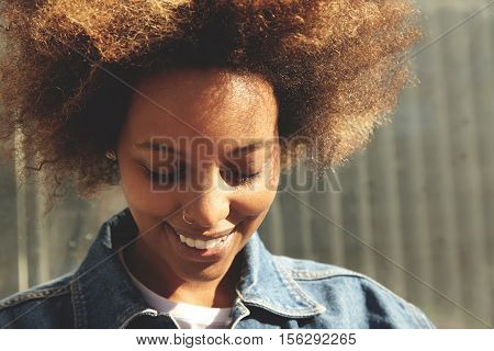 Close Up Portrait Of Happy African Student Girl With Stylish Afro Haircut And Facial Piercing Smilin