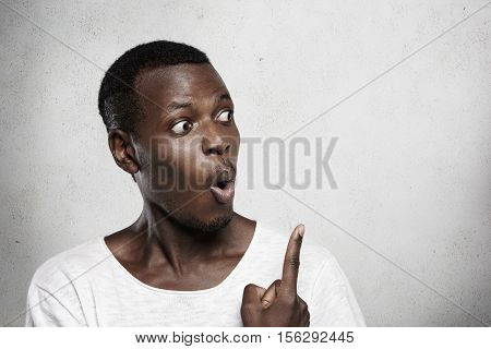 Studio Portrait Of Bug-eyed Dark-skinned Man With Amazed And Astonished Expression, Looking At Blank