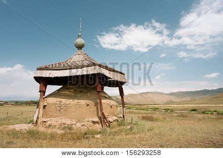 Land embankment installed as a monument in the valley between the mountains of Central Asia, Kyrgyzstan
