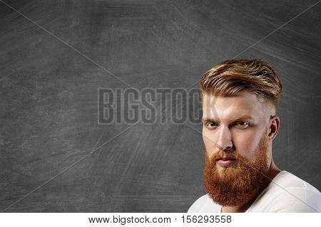 Portrait Of Caucasian Man With Stylish Haircut And Big Fuzzy Beard Wearing White T-shirt Looking At