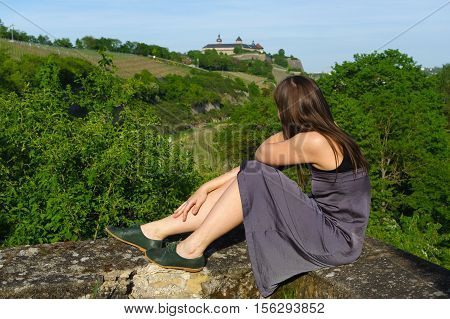 a happy girl on rock relaxing with a view to grape field landcape and the Festung or fort Marienberg in background