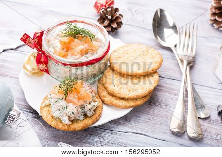 Smoked salmon, soft cheese and dill spread, mousse, pate, rillette in a jar with crackers on white wooden background. Delicious Christmas themed dinner table. Holiday concept.