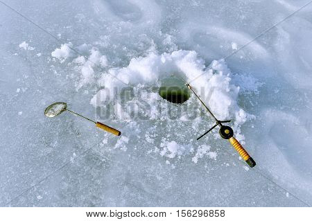 Hole in the ice on the lake and fishing rod on ice fishing