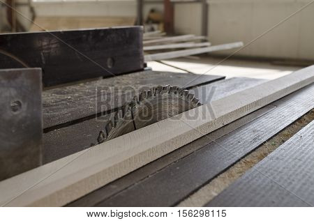 Sawing wooden plate on a workbench in the wood industry