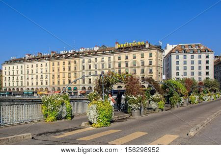 Geneva, Switzerland - 24 September, 2016: Pont des Bergues bridge over the Rhone river, buildings on the Quai des Bergues quay in the background. The city of Geneva is the capital of the Swiss Canton of Geneva.